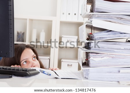 Businesswoman In Office Looking At Stack Of Folders - stock photo