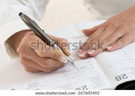 Businesswoman in office noting an appointment in her diary, closeup - stock photo