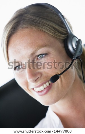 Businesswoman in office wearing headset and smiling - stock photo