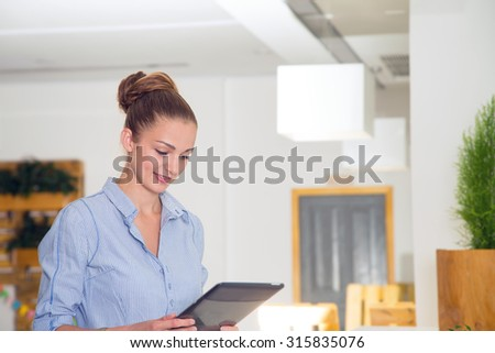 Businesswoman in office working on digital tablet. Beautiful modern business woman holding tablet computer with office on background. Business woman standing in foreground with a tablet in her hands. - stock photo