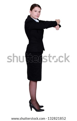 businesswoman in profile making gesture with fists - stock photo