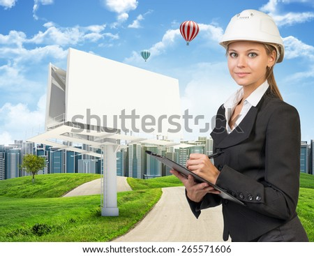 Businesswoman in suit and helmet holding clipboard, looking at camera. Large billboard, road, grass hills and city as backdrop - stock photo
