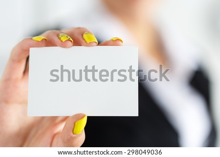 Businesswoman in suit hand holding blank calling card. Female hand showing white visiting card in camera closeup. Partners contact information exchange concept. Introducing gesture at formal meeting - stock photo