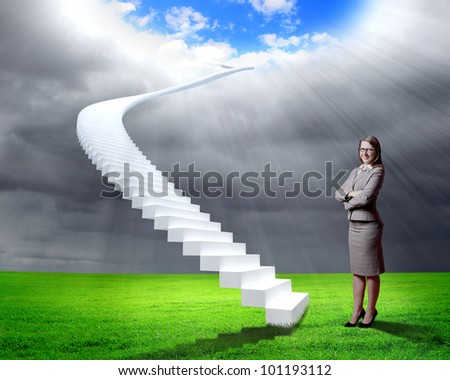 Businesswoman in suit standing near stairs going up - stock photo