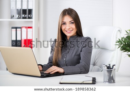Businesswoman in the office, sitting with laptop and Looking at camera. - stock photo