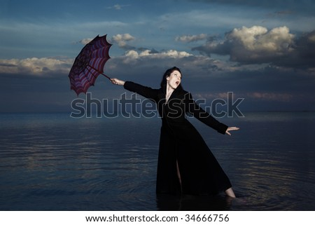 Businesswoman in the water with blown umbrella