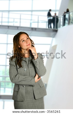 Businesswoman in thinking pose in corporate interior with business team in background. - stock photo