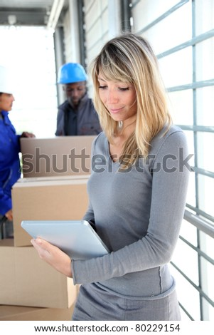 Businesswoman in warehouse using electronic tablet - stock photo