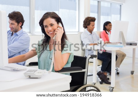 Businesswoman in wheelchair on phone in the office - stock photo