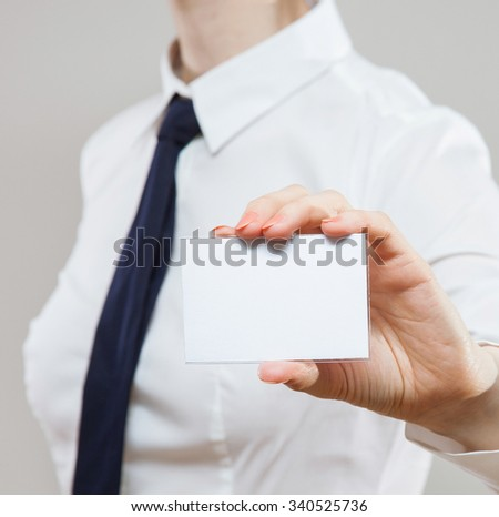 Businesswoman in wormalwear showing business card, neutral background