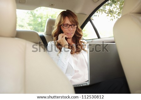Businesswoman inside her car using a laptop and a mobile phone - stock photo