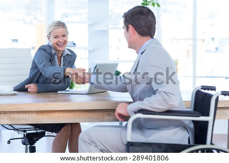 Businesswoman interviewing disabled job candidate in an office - stock photo