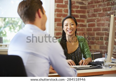 Businesswoman Interviewing Male Job Applicant In Office - stock photo
