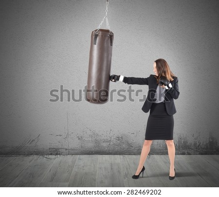 Businesswoman is boxing and punching a bag - stock photo