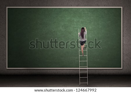 Businesswoman is climbing a ladder in front of a blackboard - stock photo