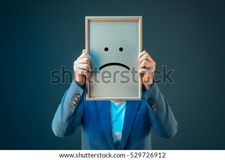 Businesswoman is pessimistic about her future in corporate business, holding printed sad smiley emoticon over her face