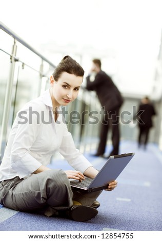 Businesswoman is sitting on the floor with notebook on her lap - stock photo