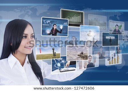 Businesswoman is using digital touchscreen to choose photos/pictures - stock photo
