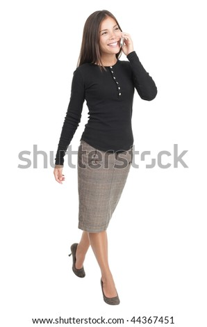 Businesswoman isolated walking in full length with mobile phone. Casual beautiful young mixed race chinese / caucasian business woman isolated on seamless white background.