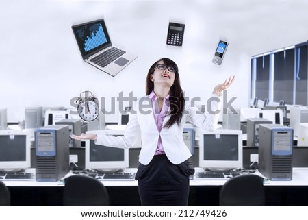 Businesswoman juggling responsibilities in the office - stock photo