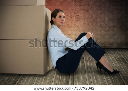Businesswoman leaning on cardboard boxes against white background against grimy room