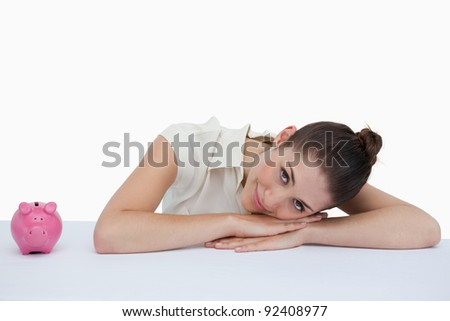 Businesswoman leaning on her desk with a piggy bank against a white background - stock photo