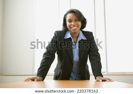Businesswoman leaning over her desk - stock photo