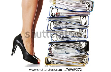 Businesswoman legs standing next to pile of ring binders. Stuck in work concept - stock photo
