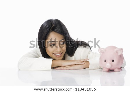 Businesswoman looking at a piggy bank - stock photo