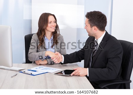 Businesswoman Looking At Businessman While Shaking Hand At Office Desk - stock photo