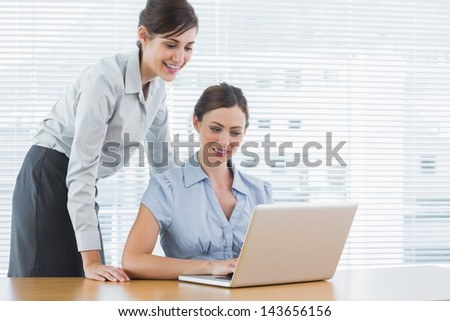 Businesswoman looking at co workers laptop at desk in office - stock photo