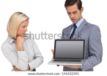 Businesswoman looking at laptop held by her colleague on white background