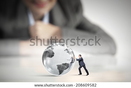 Businesswoman looking at miniature of businessman rolling planet