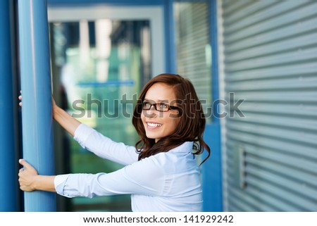 Businesswoman looking at something and holding a blue post - stock photo