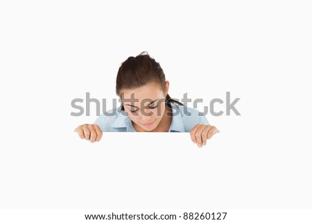 Businesswoman looking down on sign against a white background - stock photo