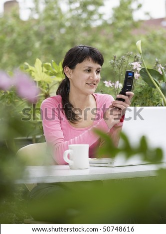 Businesswoman looking happily at Cell Phone with white laptop in garden - stock photo