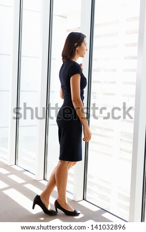 Businesswoman Looking Out Of Office Window - stock photo