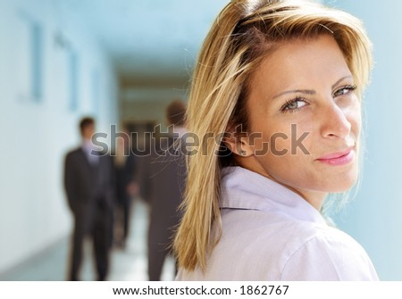 businesswoman looking over her shoulder, blurry businessmen in the background - stock photo