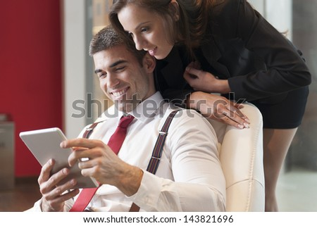 Businesswoman looking over male colleagues shoulder pointing at digital tablet - stock photo