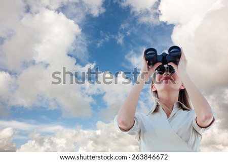Businesswoman looking through binoculars against blue sky with white clouds