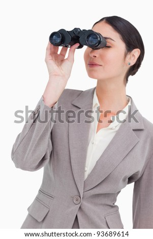 Businesswoman looking through spy glasses against a white background