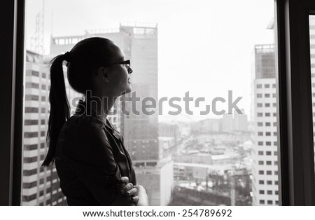 Businesswoman looking through the window - stock photo