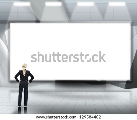 Businesswoman looking up at large blank screen under lights on grey background