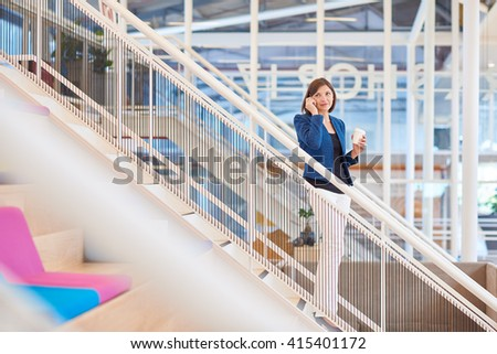 Businesswoman looking up while on phone in bright modern office - stock photo