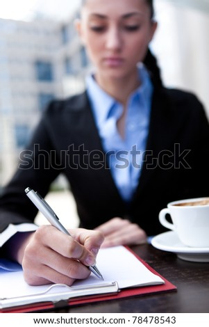 businesswoman make notice on coffee break - stock photo