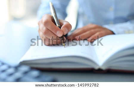 Businesswoman makes a note in notebook.  - stock photo