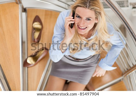 Businesswoman making a phone call and sitting on the stairs in her apartment - stock photo