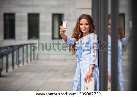 Businesswoman making selfies near office block. Pretty successful lady in blue coat posing outdoors. - stock photo