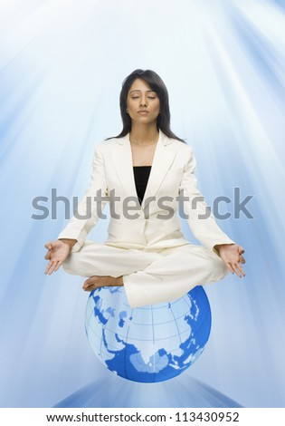 Businesswoman meditating on a globe - stock photo