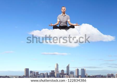 Businesswoman meditating sitting on the white cloud - stock photo